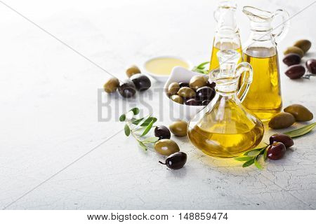 Olive oil in vintage bottles with black and green olives and leaves copyspace on white background