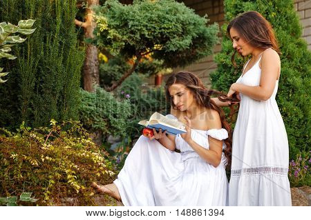 Two sisters. She reads a book and her sister her plait braids. Girls in long white dresses. Family time in the backyard.