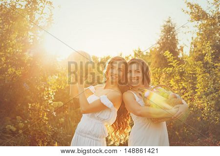 Two cute sisters in long white dresses hold in hands of the crop. Girl holding a basket of ripe fruits and vegetables and the other girl is holding a watermelon. A bountiful harvest. Agriculture. The setting sun. Soft focus