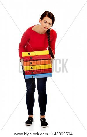 Tired young woman holding heavy binders