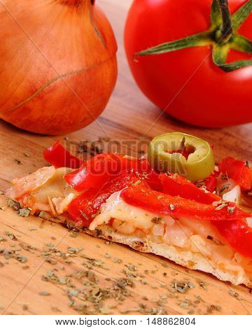Slice of fresh baked vegetarian pizza ready to eat tomatoes onion and basil on wooden table italian cuisine concept of fast food