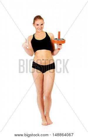 Young and sporty woman holding sport wheel and showing thumb up