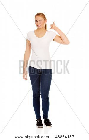 Young woman gesturing call me sign
