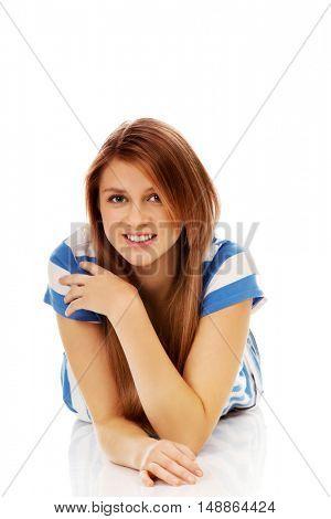 Smiling teenage woman lying on floor
