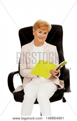 Smile elderly business woman reading a notes