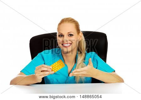 Young female nurse or doctor sitting behind the desk and holding  packet of pills