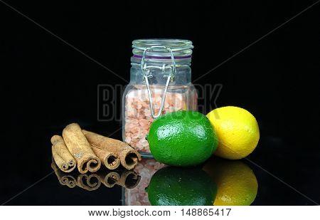 A jar of pink Himalayan salt with cinnamon sticks and lemons on a black background