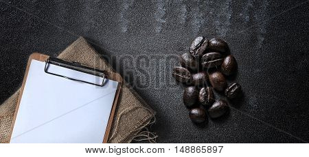 Blank clipboard on sackcloth with coffee beans on black stone background