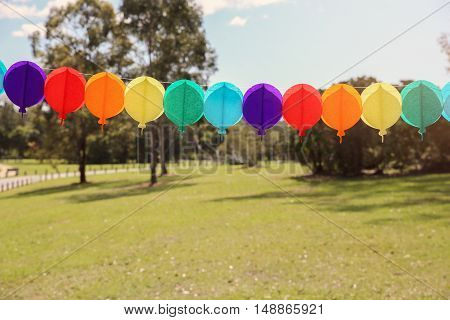 Handmade rainbow balloon bunting in the park