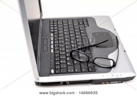 Ordenador portátil abierto con gafas negras