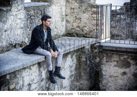 Portrait of good-looking man sitting on stone edge
