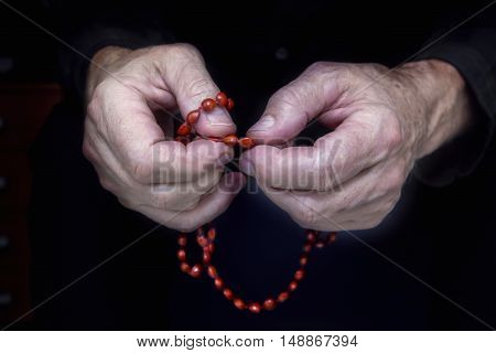 Close view of men's hands with rosary on a dark background