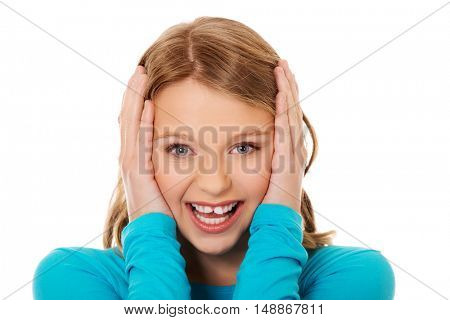 Excited young woman holding her head