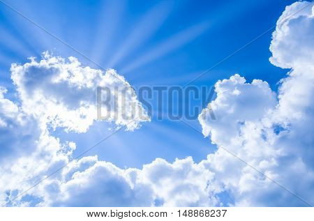 sun rays breaking through the blue sky and clouds. You can apply for sky background, sky backdrop, sky wallpaper, sky with text and everything about sky background concept.