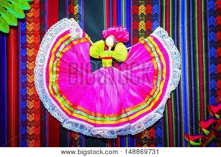 paper figure of mexican dancer on a traditional carpet