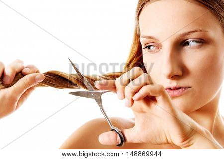 Young blonde woman cutting her hair with scissors.