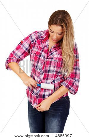 Young woman cleaning her shirt with lint roller