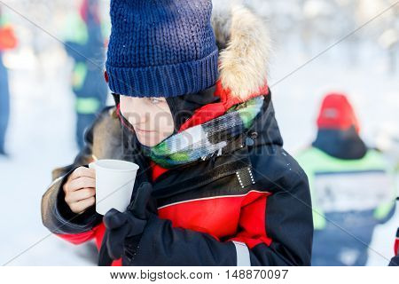 Cute boy outdoors on beautiful winter snowy day drinking hot tea