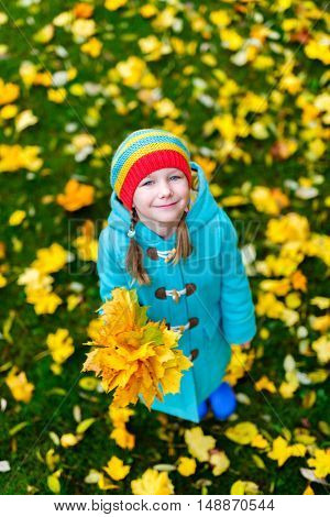 Adorable little girl with yellow maple leaves outdoors at beautiful autumn park
