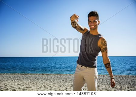 Handsome Athletic Young Man in Trendy Attire, on a Beach in a Sunny Summer Day, Smiling at Camera, Doing Middle Finger Gesture with a Smile, Looking Away against Blue Sea Background.
