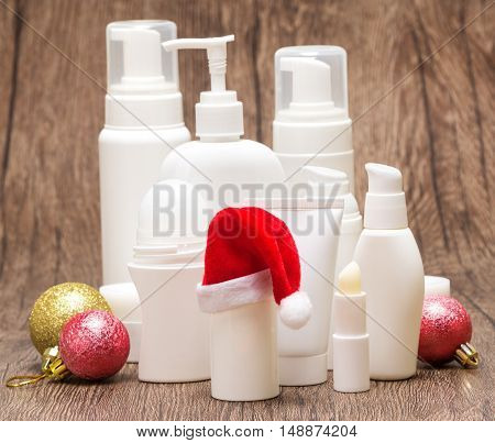 Various cosmetic products for face and body care with Santa hat and Christmas balls on wooden surface. Christmas and New Year sale or gift concept, focus on hat