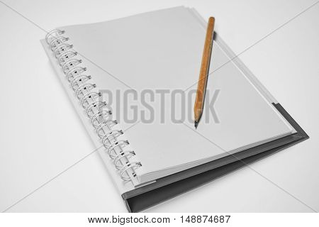 Wooden pencil put on a notebook. Selective focus on pencil which is put on the notebook in black and white background