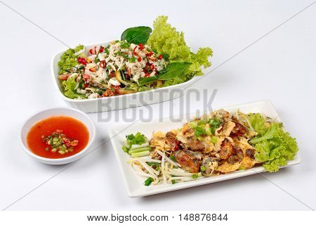 Fried oyster with herb and Spicy sour herb salad crab on brown.