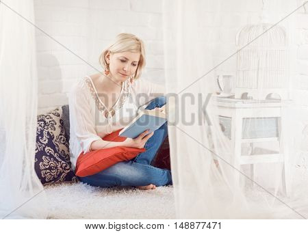 Blonde woman sitting at home on floor, reading a book.