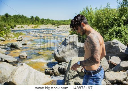 Athletic shirtless young man outdoor at river or water stream, looking away, with rocks and stones in background