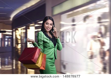 Shopping Asian Woman Talking On The Phone And Holding A Paper Bag