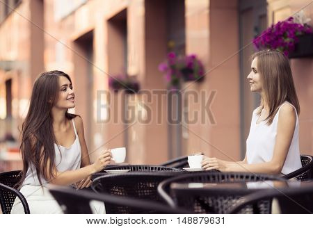 People, Communication And Friendship Concept.  Smiling Young Women Drinking Coffee Or Tea And Talking At Outdoor Cafe.