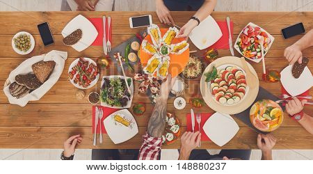 People eat grilled corn at festive table served for party. Friends celebrate with catering food on wooden table top view. Woman and man's hands take the corncobs. Mobile devices lay on desk