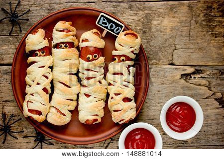 Sausage mummies in dough scary halloween food celebration party with funny eyes on vintage wooden background