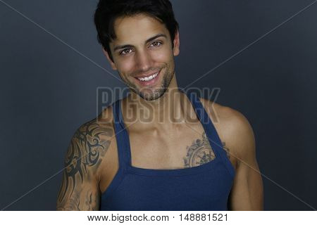 beautiful smiling man wearing a tank top over a gray background