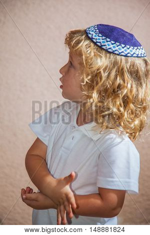 The charming little boy with long blond curls and blue eyes in the Jewish knitted yarmulke. Autumn holiday of Sukkot