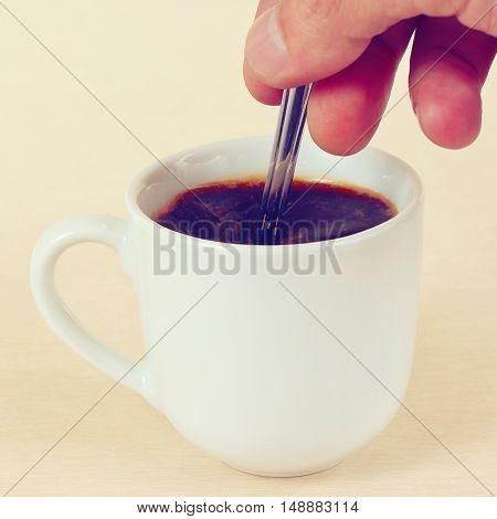 Hand mixing with a spoon of prepared coffee in the cup gently toned