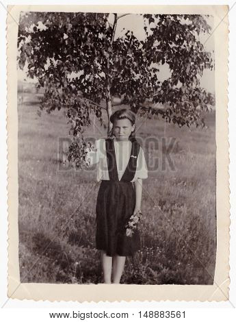 VITEBSK BELARUS - CIRCA 1953: Portrait of girl in full growth on meadow near tree (vintage photo 1953)