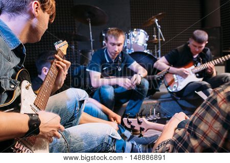 Band rehearsal before a live performance. Guitarists of music group sitting with their instruments and strum the guitar