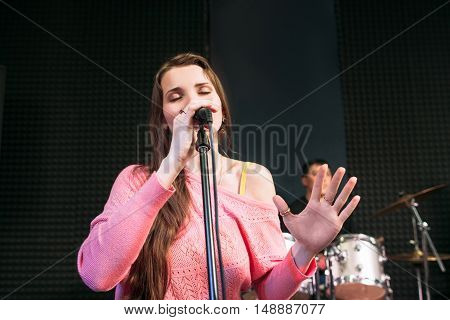 Emotionally singing into microphone woman. Female soloist perform lyric song with closed eyes. Feelings, love, leisure concept