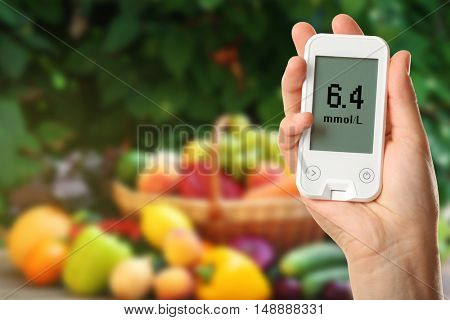 Male hand holding glucometer with fresh fruits and vegetables on table outdoors. Diabetes concept