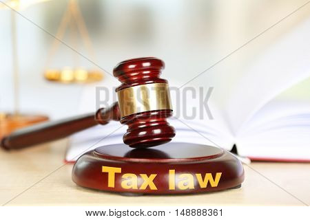 Wooden judges gavel on wooden table, close up. Tax law concept