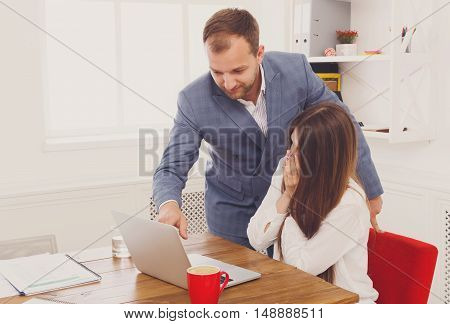 Businessman supervise and help correct his assistant's mistake in work on laptop computer. Man with woman in the office. Male boss and female secretary. Communication of manager and stuff