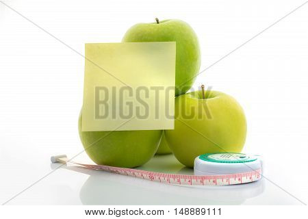 Measuring tape and green apple as a symbol of diet with note paper