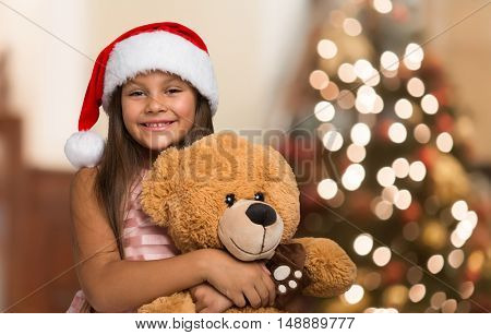 Smiling little girl wearing a Christmas hat holding a teddy bear. Christmas tree in the background