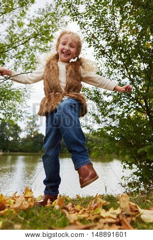 Gril having fun and dancing on leaves in autumn at the park
