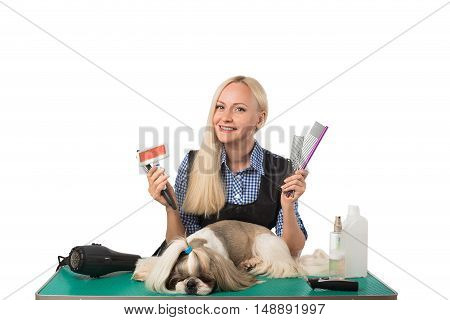 Beautiful smiling woman groomer with different combs and cute shih-tzu dog - isolated on white
