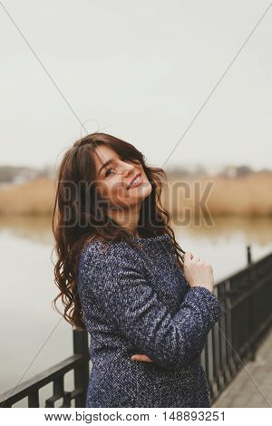 Vertical portrait close up of young beautiful brunette woman wearing a coat on fall