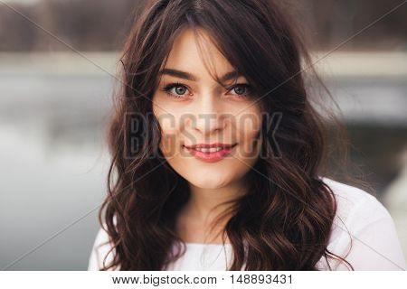 Beautiful woman face closeup. Close up portrait of young woman with natural make up smiling and looking to camera outdoors.