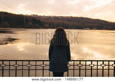 Rear view of sad woman silhouette at sunset lake. Female wearing a warm coat staying in cold weather. Loneliness and sadness concept