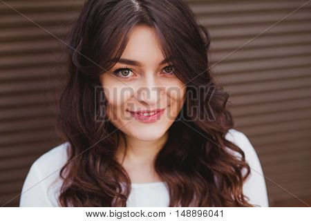 close up of a beautiful young girl with a clean fresh face. Woman with brunette curly hair and big eyes smiling over a brown wall.